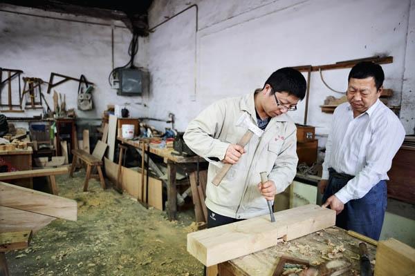 第三代工匠正在向第四代学员传授木工技艺